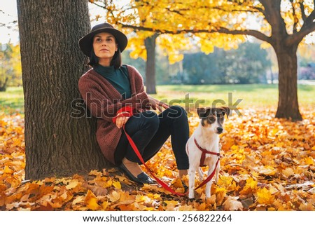 Thoughtful young woman with dog outdoors in autumn - stock photo