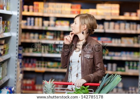 Thoughtful young woman with hand on chin looking at products in supermarket