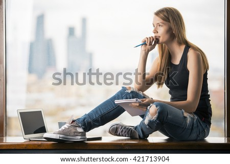 Thoughtful young woman with notepad in hand sitting on windowsill with blank laptop screen. Blurry city view in the background. Mock up - stock photo