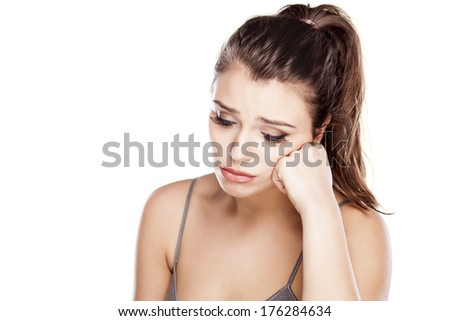 thoughtfull sad young woman on a white background - stock photo