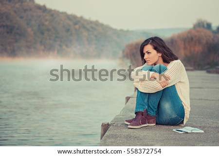 Thoughtfully woman is sitting by lake. Early morning. It's chilly outside.