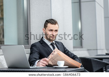 Thoughts about work. A young man sits at a table and reading a newspaper