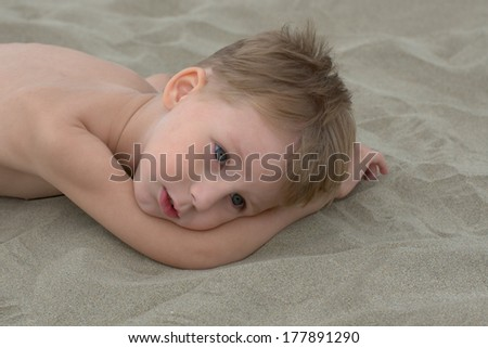 thougtful little boy lying on the sand - stock photo