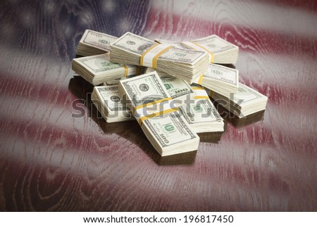 Thousands of Dollars Pile with Reflection of American Flag on Wooden Table. - stock photo