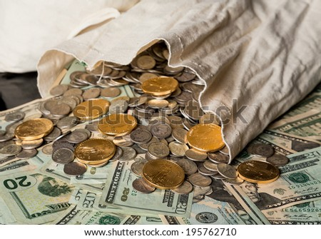 Thousands of US dollars  in notes and gold and silver coins pouring out of a cloth money bag onto a black background showing many currency notes or bills - stock photo