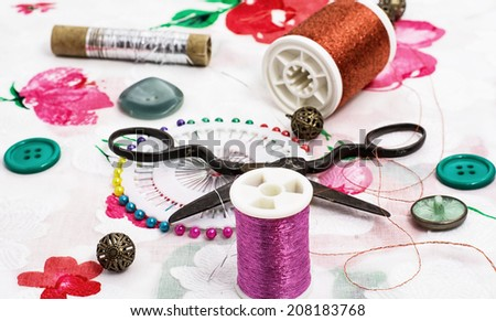 thread for sewing,buttons,scissors on a light background - stock photo