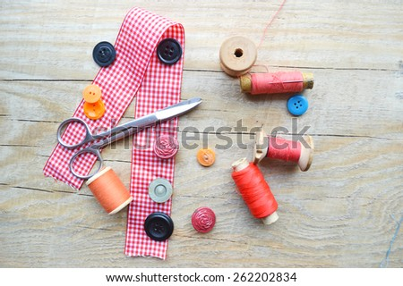 thread for sewing, supplies and accessories for sewing on a light wooden table - stock photo
