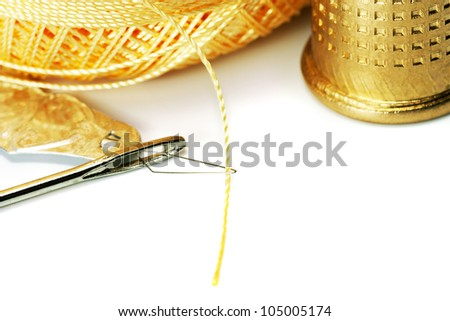 Thread in needle thimble isolated on white background - stock photo