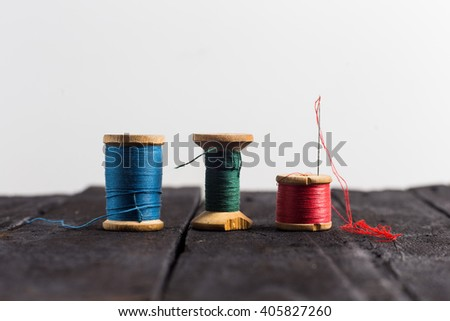 Thread with a nedle. Three: green, red and blue thread with one neeedle on black wood table.  - stock photo