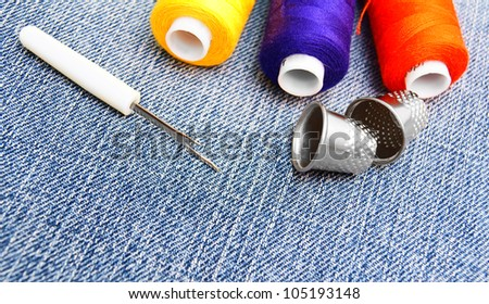 Threads and thimbles on jeans . - stock photo