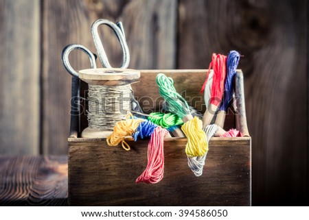 Threads, needle and scissors on tailor table - stock photo