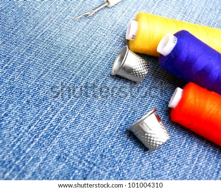 Threads, thimbles on jeans. - stock photo