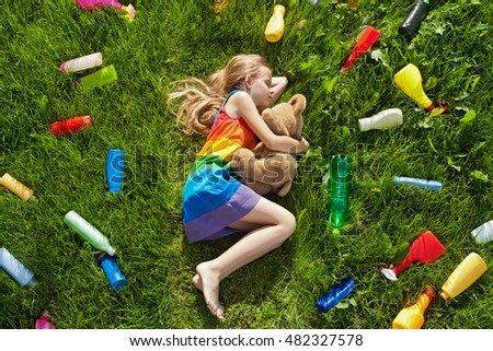 Threat to our colorful dreams - plastic litter surrounding girl sleeping in the grass