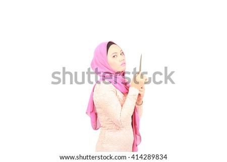 Threatening angry looking woman holding a knife in a attack position