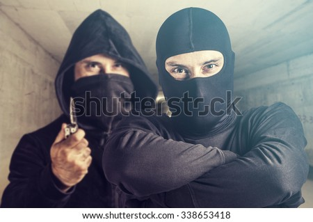 Threatening situation concept. Masked criminals. Selective focus image cross processed for dramatic look - stock photo