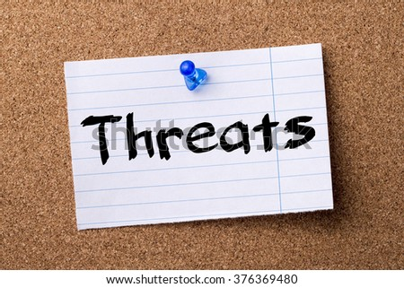 Threats - teared note paper  pinned on bulletin board - horizontal image - stock photo