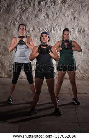 Three active females lifting large kettlebell weights - stock photo