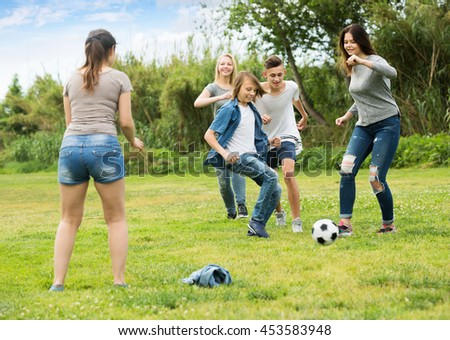 Three active girls and two boys teenagers friends running with ball on meadow outdoors - stock photo