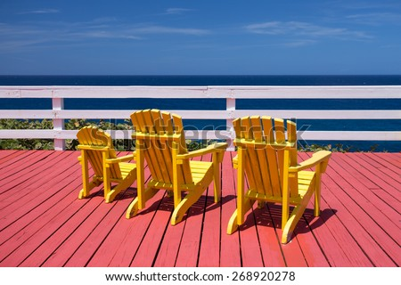 Three adirondack chairs on a red deck overlooking the ocean - stock photo