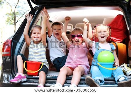 Three adorable girls and boy sit on a car trunk and laughing - stock photo