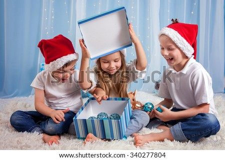 Three adorable kids, preschool children, siblings, having fun for Christmas, opening box with decoration, studio shot - stock photo