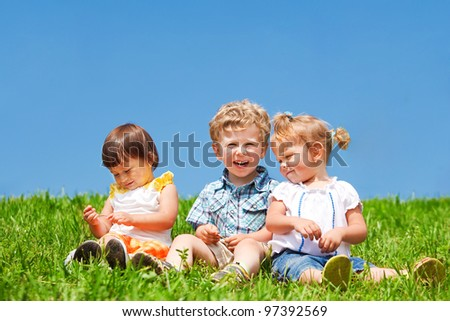 three adorable kids sit on green grass against blue sky - Pictures Of Small Kids