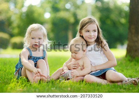 Three adorable little kids having fun outdoors on a sunny summer day - stock photo