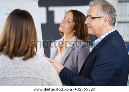 Three adult business people discussing metrics or marketing strategy while standing in front of chart at office - stock photo