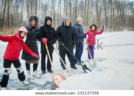 Three adults and three children going to clean outdoor skating rink surface from snow.