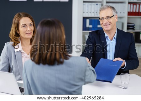 Three adults closing an important business transaction or negotiation and exchanging documents while seated at table in office - stock photo
