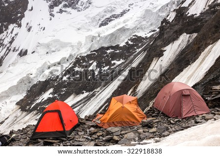 Three Alpine Tents Settled on Edge of Abyss Mountain Climbers Camp on Rock Moraine of Glacier High Altitude Severe Landscape - stock photo