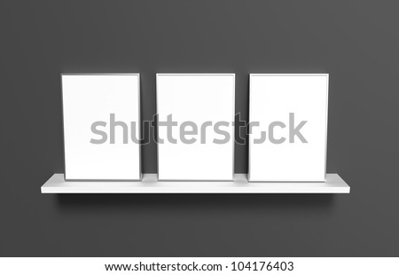 Three aluminum frames with blank images, standing besides each other on a white shelf on a dark background.