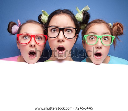 Three amazed teens with blank presentation board
