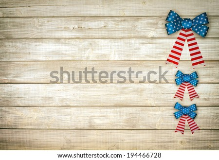 Three American Flag Glitter Bows on side of Rustic White Board Background with room or space for copy, text.  Horizontal, grunge vintage sepia processing. - stock photo