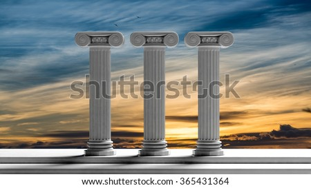 Three ancient pillars with sunset sky background. - stock photo