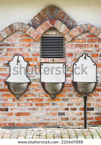 Three ancient wash basin on a red brick wall  - stock photo