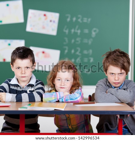 Three annoyed children sitting in the classroom - stock photo