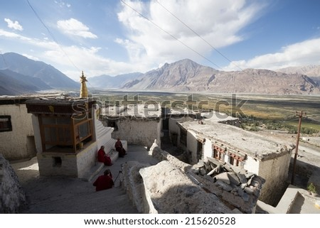 Three anonymous monks sitting in a monastery viewing over Nubra Valley, India. - stock photo