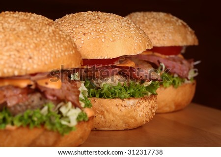 Three appetizing big delicious fresh burgers with green lettuce red tomato cheese cabbage bacon slice meat cutlet and white bread bun with sesame seeds on black background closeup, horizontal picture - stock photo