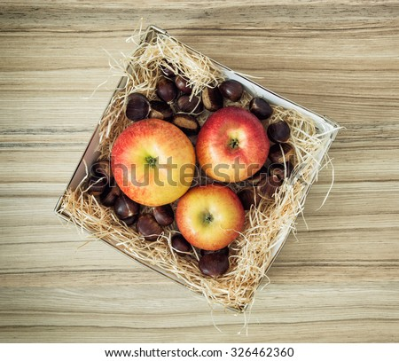 Three apples and chestnuts in the box on the wooden background. - stock photo