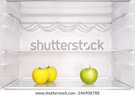 three apples in open empty refrigerator - stock photo