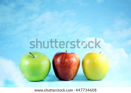 Three apples on bright sky and clouds. - stock photo