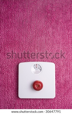 Three apples placed on scales, shot portrait. - stock photo