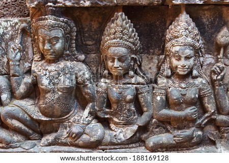Three apsara statue on the wall of Angkor temple - stock photo