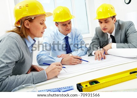 Three architects sitting at table and discussing paperwork - stock photo
