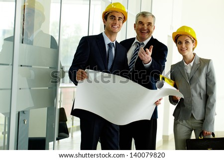 Three architects standing in office building and ooking at camera while planning work