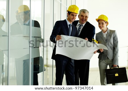 Three architects standing in office building and planning work - stock photo