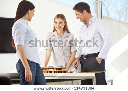 Three architects with a building model in 3D in their office - stock photo