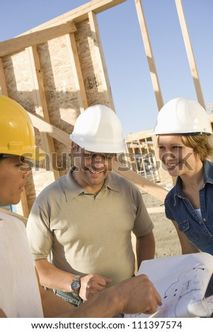 Three architects with blueprint discussing at construction site