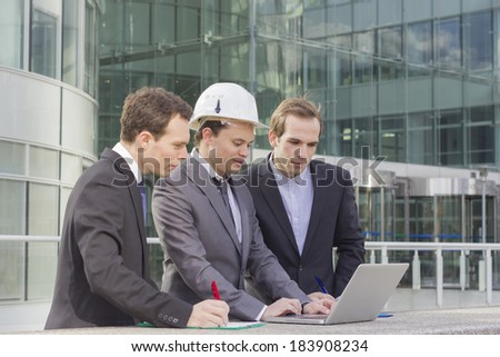three architects working on computer wearing helmet in front of glass building - stock photo
